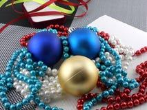 Weihnachtsball und -perlen auf einer Platte, Karte des neuen Jahres Lizenzfreies Stockfoto