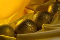 Weihnachtsballdekoration auf einem gelben Satinstoff lizenzfreie stockbilder