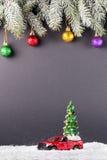 Weihnachtsbaum auf Spielzeug rotem LKW-Auto auf Schnee, Ballweihnachten-tre Lizenzfreie Stockfotos
