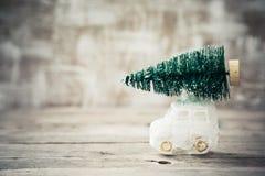 Weihnachtsbaum auf Spielzeugauto Abstraktes Hintergrundmuster der weißen Sterne auf dunkelroter Auslegung Bänder auf gelbem Hinte Stockfoto