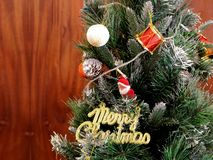 Weihnachtsbaum-Dekorationen mit Sankt und frohe Weihnacht-Text-Zeichen - Weihnachtskarten-Entwurf stockfoto