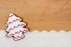 Weihnachtsbaum formte Plätzchen, gewirkten Schnee auf hölzernem backgroun Stockbilder