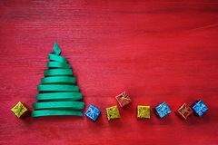 Weihnachtsbaum gemacht vom grünen Band mit kleinen Geschenken auf rotem Hintergrund Lizenzfreie Stockfotos
