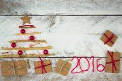 Weihnachtsbaum gemacht vom Pappgeschenk auf hölzernem Hintergrund Lizenzfreies Stockfoto