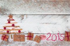 Weihnachtsbaum gemacht vom Pappgeschenk auf hölzernem Hintergrund Lizenzfreie Stockbilder