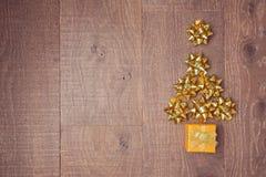 Weihnachtsbaum gemacht von den dekorativen Bögen und von den Geschenkboxen auf hölzernem Hintergrund Ansicht von oben Stockfotos