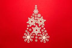 Weihnachtsbaum gemacht von den Schneeflocken auf einem roten Hintergrund lizenzfreie stockbilder