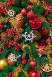 Weihnachtsbaum - grüne Kiefernniederlassungen und rote Kugel und Kiefernkegel im Gold Lizenzfreies Stockfoto