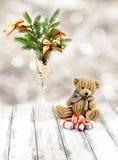Weihnachtsbaum im weißen dekorativen Becher, weiße und rote Geschenkbox, brauner Spielzeugbär und Schnee auf Retro- Weinleseweißt Stockfotografie