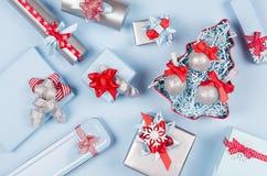 Weihnachtsbaum mit Funkelnbällen und Geschenkboxen, Dekorationen in der blauen und silbernen metallischen Pastellfarbe mit roten  stockfoto