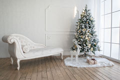 Weihnachtsbaum mit Geschenken darunterliegend im Wohnzimmer Lizenzfreie Stockbilder