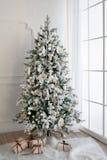 Weihnachtsbaum mit Geschenken darunterliegend im Wohnzimmer Stockbild