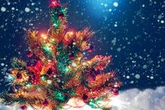 Weihnachtsbaum mit Girlande von Lichtern und von Dekorationen Stockfotografie