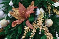 Weihnachtsbaum mit goldenen Bällen und Blättern, orange Blume orna Stockfotografie