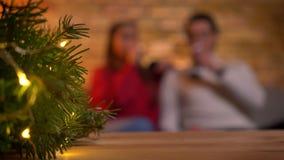 Weihnachtsbaum mit hellen Lichtern und unscharfen jungen den Paaren, die auf Sofa sitzen und auf Hintergrund sprechen stock video