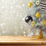 Weihnachtsbaum und Dekorationen über bokeh Lichthintergrund Schwarze, goldene und silberne Verzierungen Stockbild