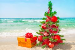 Weihnachtsbaum und goldenes Geschenk mit großem rotem Bogen auf dem Meer setzen auf den Strand Stockfoto