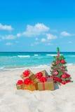 Weihnachtsbaum und goldenes Geschenk mit großem rotem Bogen auf dem Meer setzen auf den Strand Stockfotografie