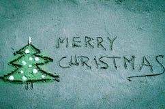 Weihnachtsbaum und Wörter der frohen Weihnachten gezeichnet in Sand Lizenzfreie Stockfotografie