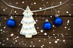 Weihnachtsbaum und Weihnachtsbälle, die an einer Linie auf Holz hängen Stockfotos