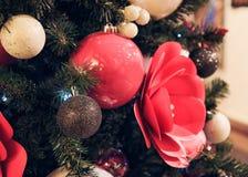 Weihnachtsbaum verziert mit roten Blumen und Weihnachtsbällen Stockfotografie