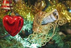 Weihnachtsbaum verziert mit Spielwaren und Geld Rotes Herz und Dollar im Kinderwagen Lizenzfreie Stockbilder