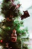 Weihnachtsbaum verziert mit Weinlesespielwaren, Abschluss oben, Fee, Bären, Zug, Einhorn und einer Girlande auf dem grünen Hinter stockbilder