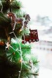 Weihnachtsbaum verziert mit Weinlesespielwaren, Abschluss oben, Fee, Bären, Zug, Einhorn und einer Girlande auf dem grünen Hinter stockbild