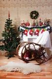 Weihnachtsbaum, verzierter Kamin und Schaukelstuhl im Innenraum Stockfotografie