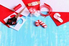 Weihnachtsbaum-Zuckerstangedekoration gemacht vom Weißfilz und vom roten Band FilzZuckerstangehandwerk, nähende Materialien Lizenzfreies Stockbild