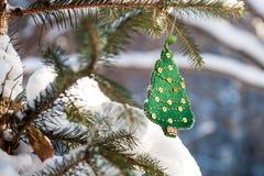 Weihnachtsbaumast im Wald mit grüner handgemachter Dekoration Sonniger Wintertag Stockfotos