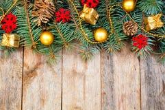Weihnachtsbaumaste mit Kegeln, Geschenken und Spielwaren auf einem backgrou Lizenzfreie Stockbilder
