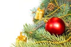 Weihnachtsbaumaste mit Kegeln, Geschenken und Spielwaren auf einem weißen Ba Lizenzfreies Stockfoto