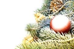 Weihnachtsbaumaste mit Kegeln, Geschenken und Spielwaren auf einem weißen Ba Stockbilder