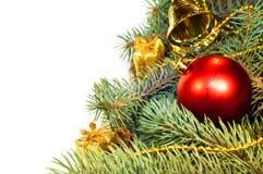Weihnachtsbaumaste mit Kegeln, Geschenken und Spielwaren auf einem weißen Ba Stockfoto