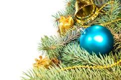Weihnachtsbaumaste mit Kegeln, Geschenken und Spielwaren auf einem weißen Ba Lizenzfreies Stockbild