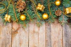 Weihnachtsbaumaste mit Kegeln, Geschenken und Spielwaren auf einem weißen Ba Lizenzfreie Stockbilder