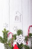 Weihnachtsbaumaste, Zuckerstangen, dekorative Schneeflocken und ein kleines Haus auf einem weißen Hintergrund Draufsicht, freier  Lizenzfreies Stockbild