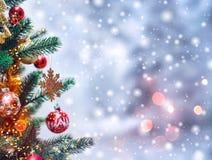 Weihnachtsbaumhintergrund und Weihnachtsdekorationen mit Schnee, verwischt, Funken, glühend Lizenzfreies Stockfoto