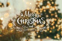 Weihnachtsbaumhintergrund und Weihnachtsdekorationen mit verwischt, Funken, Glühen und Text frohe Weihnachten und guten Rutsch in lizenzfreies stockbild