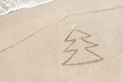 Weihnachtsbaumkontur mit Stern und Welle auf dem Strand Stockbild