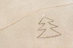 Weihnachtsbaumkontur mit Stern und Welle auf dem Strand Lizenzfreie Stockfotografie