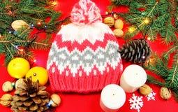Weihnachtsbaumspielwaren auf einer roten Serviette Mandarinen und Kerzen auf Th stockfotografie