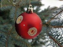 Weihnachtsbaumspielzeug auf einer Niederlassung im Winter auf einem Hintergrund des Schnees lizenzfreies stockfoto