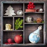 Weihnachtsbehälter mit Spielwaren. Antike Uhr, Schneemann und Bälle. Stockfotos