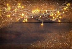 Weihnachtsbeleuchtet warme Goldgirlande auf hölzernem rustikalem Hintergrund gefiltertes Bild mit Funkelnüberlagerung Stockfotos