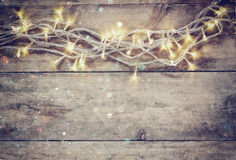 Weihnachtsbeleuchtet warme Goldgirlande auf hölzernem rustikalem Hintergrund gefiltertes Bild mit Funkelnüberlagerung Lizenzfreies Stockfoto