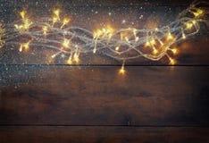 Weihnachtsbeleuchtet warme Goldgirlande auf hölzernem rustikalem Hintergrund gefiltertes Bild mit Funkelnüberlagerung Stockbild