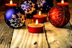 Weihnachtsblaue und rote Bälle mit brennenden Kerzen auf beunruhigtem hölzernem Hintergrund lizenzfreie stockbilder