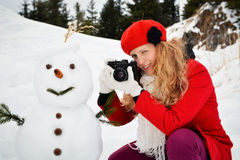 Weihnachtsblondes Mädchen und ein Schneemann Stockfotografie